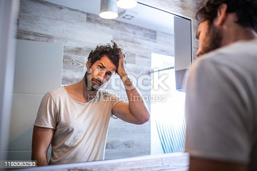1130731761 istock photo Handsome young man touching his hair with hand and grooming in bathroom at home. White metrosexual man worried for hair loss and looking at mirror his receding hairline. 1193083293