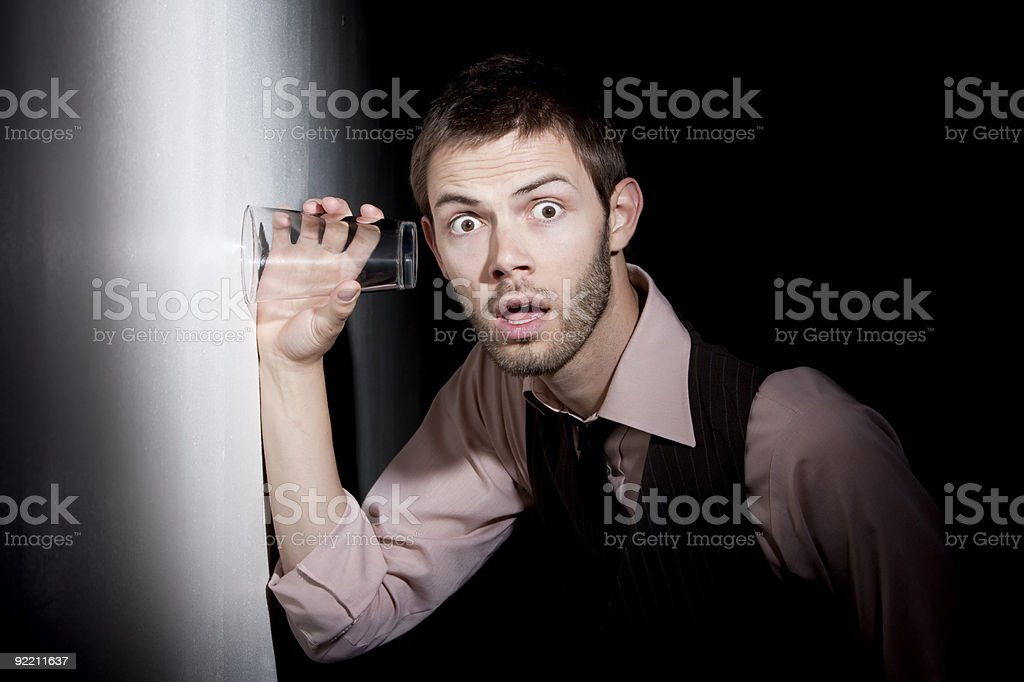 Handsome young man using glass to eavesdrop royalty-free stock photo