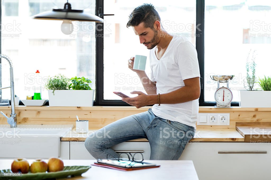 Handsome young man using his mobile phone in the kitchen. stock photo