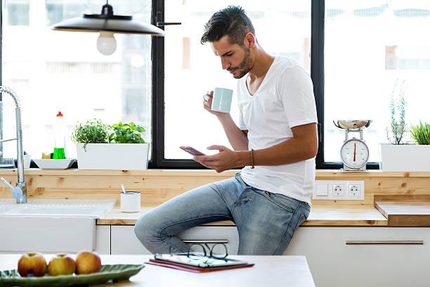 handsome young man using his mobile phone in the kitchen. - gesichtertassen stock-fotos und bilder