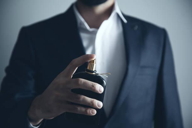 przystojny młody mężczyzna używający perfum - perfumowany zdjęcia i obrazy z banku zdjęć