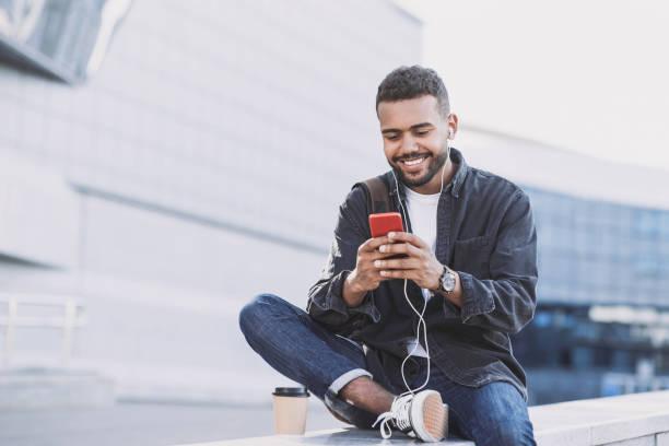 Schöne junge Mann mit Smartphone in einer Stadt – Foto