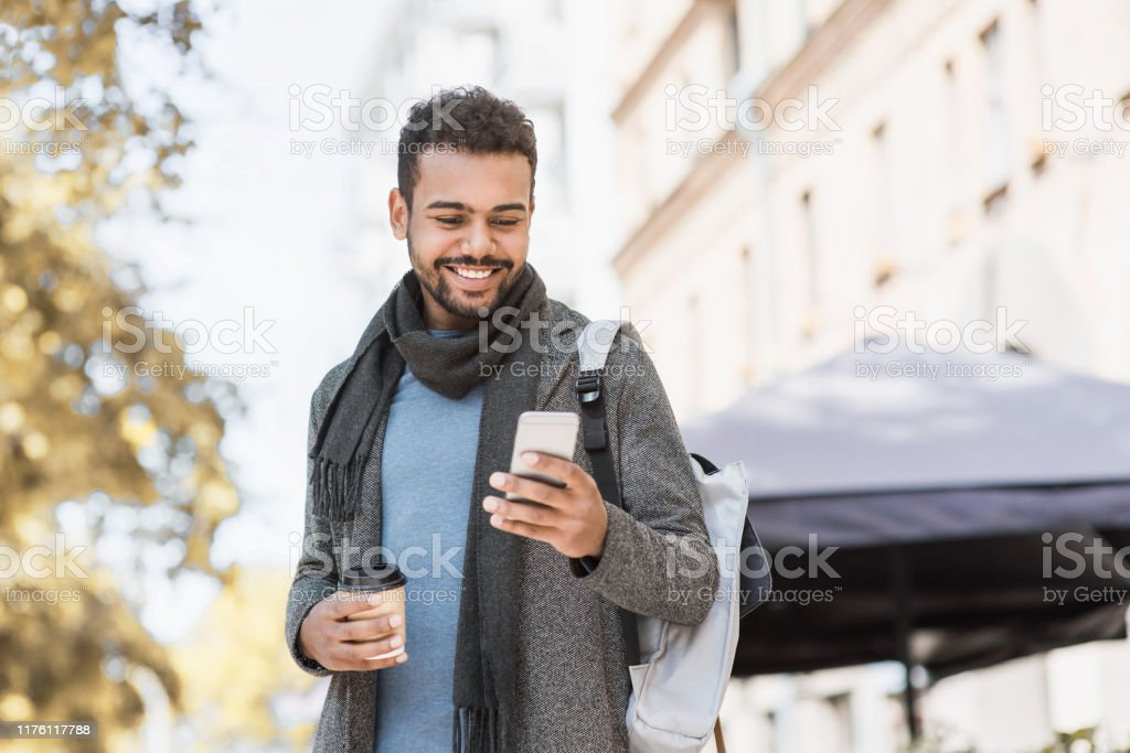 Handsome young man using smart phone in a city Student men using mobile phone on a city street. Freelance work, communication, business concept 20-29 Years Stock Photo