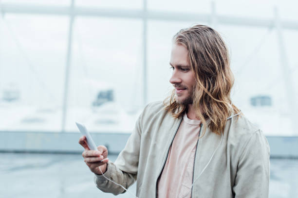 handsome young man using smartphone on street on cloudy day handsome young man using smartphone on street on cloudy day medium length hair stock pictures, royalty-free photos & images