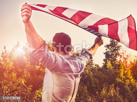 514069232 istock photo Handsome, young man waving an American flag 1147128293