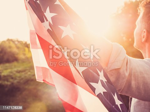 514069232 istock photo Handsome, young man waving an American flag 1147128338
