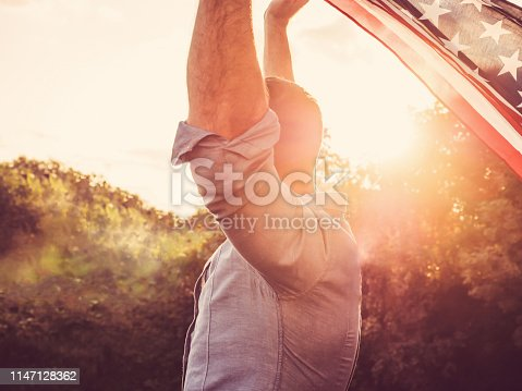 514069232 istock photo Handsome, young man waving an American flag 1147128362