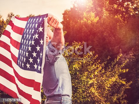 514069232 istock photo Handsome, young man waving an American flag 1147579783