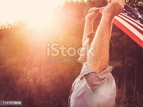 514069232 istock photo Handsome, young man waving an American flag 1147579938
