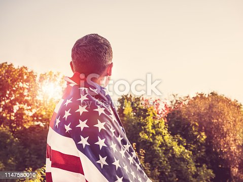 514069232 istock photo Handsome, young man waving an American flag 1147580010