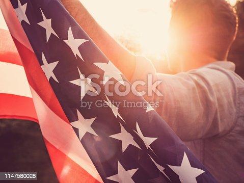 514069232 istock photo Handsome, young man waving an American flag 1147580028