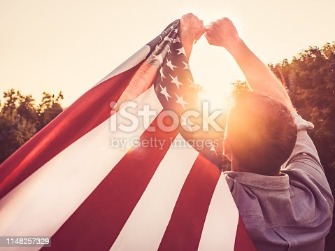 514069232 istock photo Handsome, young man waving an American flag 1148257329