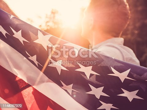 514069232 istock photo Handsome, young man waving an American flag 1148257370