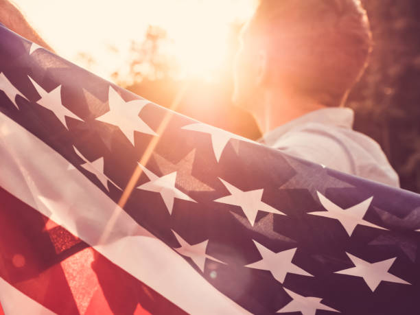 Handsome, young man waving an American flag stock photo