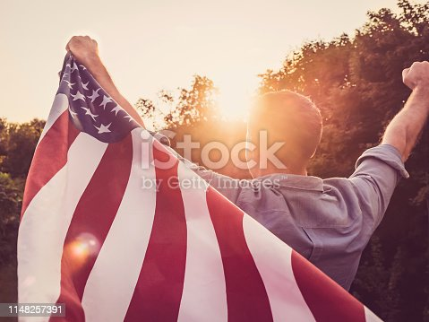 514069232 istock photo Handsome, young man waving an American flag 1148257391