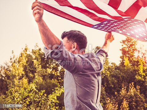 514069232 istock photo Handsome, young man waving an American flag 1148257566