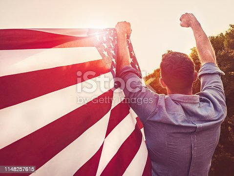 514069232 istock photo Handsome, young man waving an American flag 1148257615