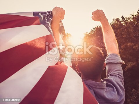514069232 istock photo Handsome, young man waving an American flag 1150340887