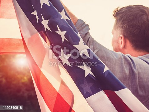 514069232 istock photo Handsome, young man waving an American flag 1150340918