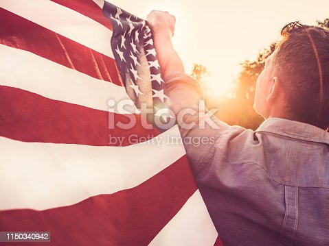 514069232istockphoto Handsome, young man waving an American flag 1150340942