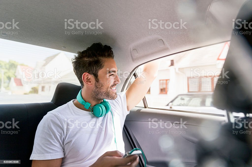 Handsome young man waving from car stock photo