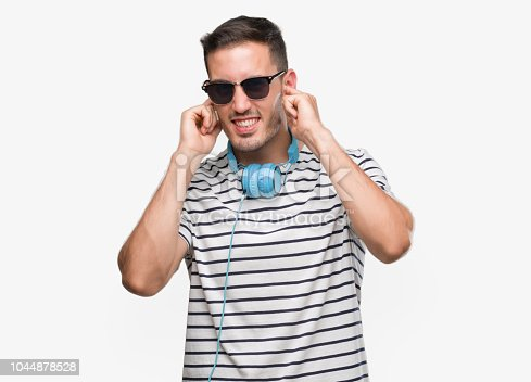Handsome young man wearing headphones covering ears with fingers with annoyed expression for the noise of loud music. Deaf concept.