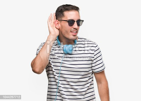 Handsome young man wearing headphones smiling with hand over ear listening an hearing to rumor or gossip. Deafness concept.