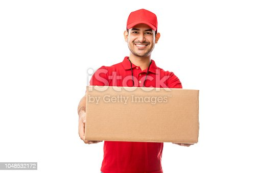 Handsome young man wearing red uniform delivering package over white background