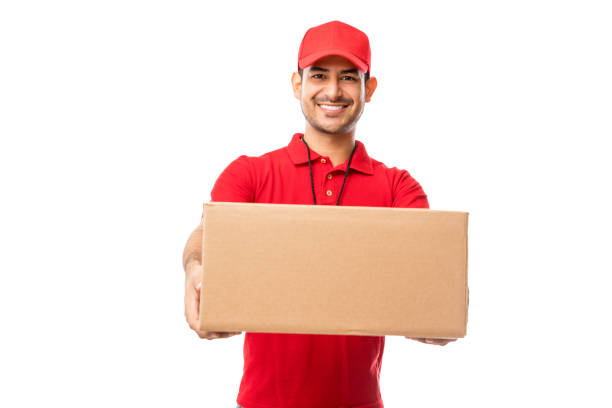 Handsome Young Man Wearing Red Uniform Delivering Package Handsome young man wearing red uniform delivering package over white background delivery man stock pictures, royalty-free photos & images