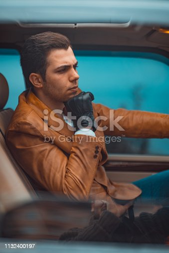 Handsome young man while driving a car. Male driver while sitting in a car with open front window