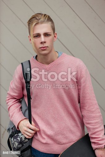 846124694 istock photo Handsome young man with a backpack and skateboard on the beach near a wooden wall 846126860