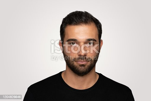 Handsome young man with blank expression..Young man looking at camera with blank facial expression .Copyspace for ads.Over isolated background .Studio shot, isolated background,horizontal composition.Young man wearing black tshirt and he has short and black hair.