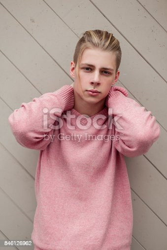 846124694 istock photo handsome young man with blond hair in a fashion pink sweater near a wooden wall 846126962