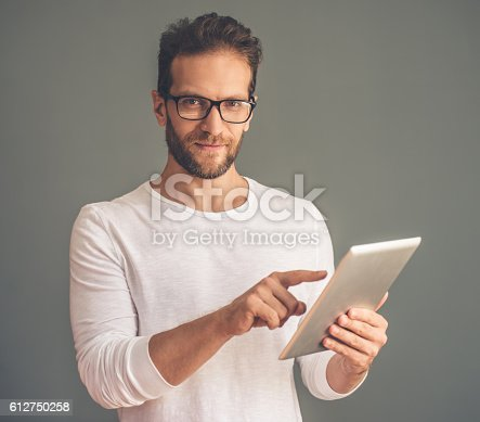 612752180istockphoto Handsome young man with gadget 612750258
