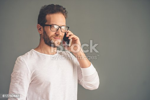 612752180istockphoto Handsome young man with gadget 612750442