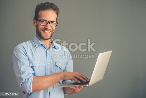 612752180istockphoto Handsome young man with gadget 612751742