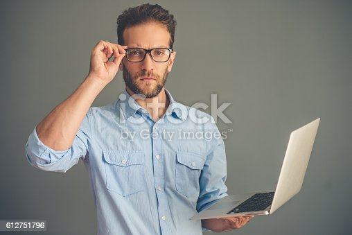 612752180istockphoto Handsome young man with gadget 612751796
