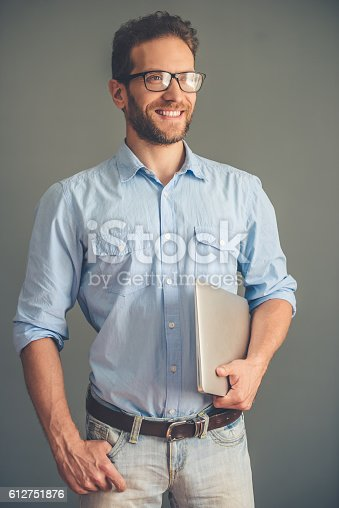 612752180istockphoto Handsome young man with gadget 612751876