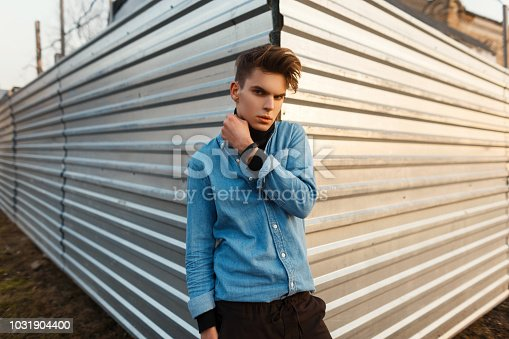 846124694istockphoto Handsome young man with hairstyle in the fashion denim shirt stands near a metal wall 1031904400