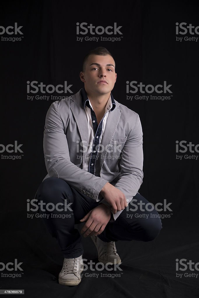 Handsome young man with jacket sitting on his heels stock photo
