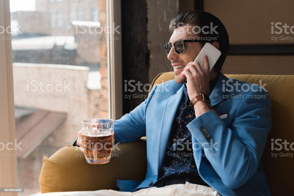 handsome young man with mug of beer talking by phone while sitting on couch royalty-free stock photo