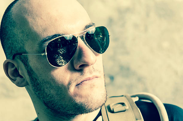 Handsome Young Man with Sunglasses and Shaved Head Close up stock photo