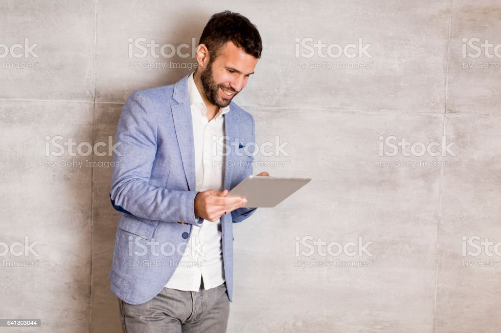Handsome young man with tablet stock photo