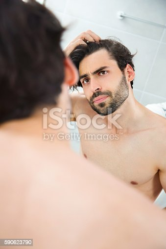 1130731761istockphoto Handsome young man worried about hair loss. 590623790
