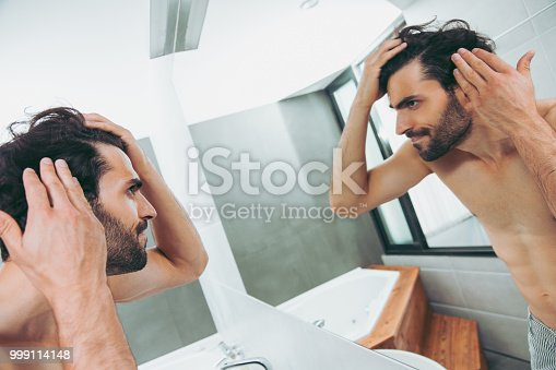 1130731761istockphoto Handsome young man worried about hair loss 999114148