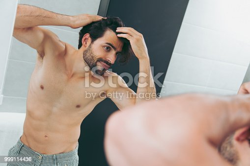 1130731761istockphoto Handsome young man worried about hair loss 999114436