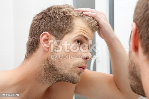 istock Handsome young man worried about hairloss 522436975