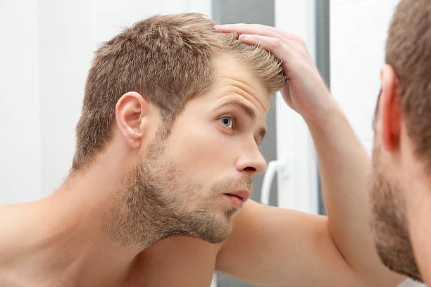 Handsome young man worried about hairloss Handsome unshaven man looking into the mirror in bathroom hair stubble stock pictures, royalty-free photos & images
