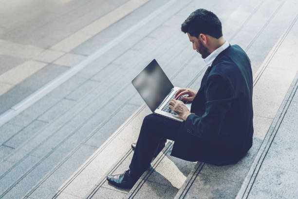 Handsome young manager working on laptop while sitting outdoors on the stairs, concept of work life balance. stock photo