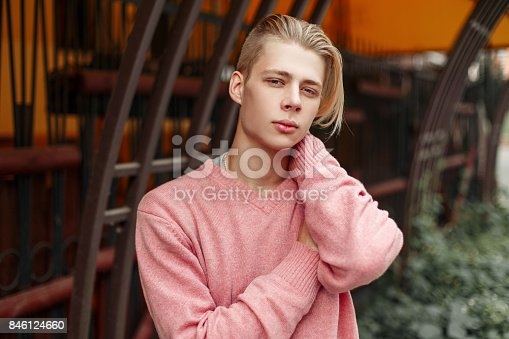 846124694 istock photo Handsome young model man with a blond hairstyle in a pink sweater on the street 846124660